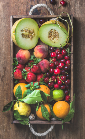 Healthy summer fruit variety. Melon, sweet cherries, peach, strawberry, orange and lemon in wooden tray over rustic wooden background, top view, vertical composition