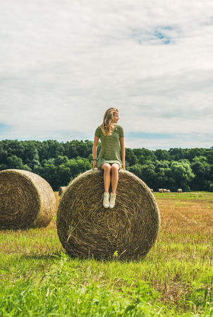 haymow: Young blond lady sitting on haystack and looking away on sunny summer day, Badasconytomaj, Hungary Stock Photo