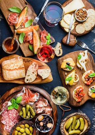 Italian antipasti wine snacks set. Brushettas, cheese variety, Mediterrnean olives, pickles, Prosciutto di Parma with melon, salami and wine in glasses over black grunge background. Top view Banco de Imagens