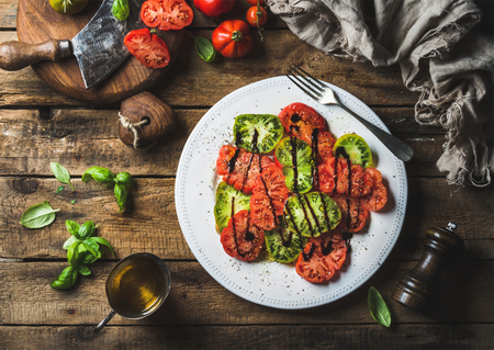 pepperbox: Heirloom tomato salad with olive oil, balsamic vinegar and basil over old rustic wooden background, top view, horizontal composition Stock Photo