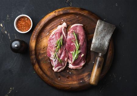 Raw ongekookt pluimveevlees snijden. Eendenborst met rozemarijn, kruiden en slager hakmes op donkere houten dienblad over zwarte houten achtergrond, bovenaanzicht Stockfoto