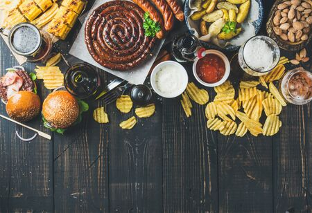 fried food: Beer and snack set. Octoberfest food frame concept. Variety of beers, grilled sausages, burgers, corn, fried potatoes, chips, salted almonds and sauces on dark wooden background. Top view, copy space