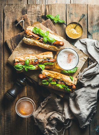 unfiltered: Glasses of wheat unfiltered beer and grilled sausage dogs in baguette with mustard, caramelised onion and herbs on serving board over rustic wooden background, top view, vertical composition