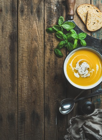 Pumpkin cream soup in bowl with fresh basil, spices and grilled bread slices over old rustic wooden background, top view, copy space, vertical composition