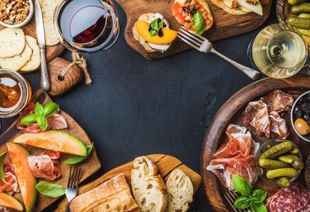 Italienische Antipasti Wein Snacks-Set. Brushettas, Käsesorte, mediterranen Oliven, Gurken, Prosciutto di Parma mit Melone, Salami und Wein in den Gläsern auf schwarzem Grunge-Hintergrund, Ansicht von oben, Kopier-Raum