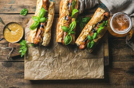 pepperbox: Glass of wheat unfiltered beer and grilled sausage dogs in baguette on baking paper with mustard, caramelised onion and herbs on serving board over rustic wooden background, top view, copy space