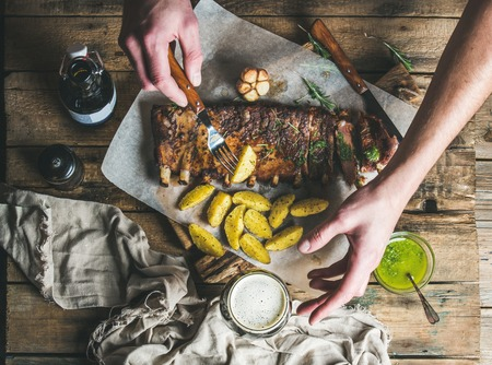 pepperbox: Man eating roasted pork ribs with garlic, rosemary and green herb sauce on rustic wooden table. Man s hand holding fork with fried potato and reaching for glass of dark beer, top view