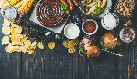 pepperbox: Beer and snack set. Octoberfest food frame concept. Variety of beers, grilled sausages, burgers, fried potato, corn, chips and sauces on dark wooden scorched background. Top view, copy space Stock Photo