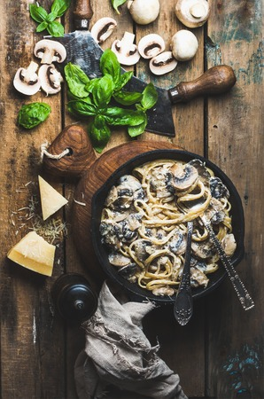 pepperbox: Italian style dinner. Creamy mushroom pasta spaghetti in cast iron pan on wooden boards with Parmesan cheese, fresh basil leaves and pepper over old rustic background. Top view, vertical composition