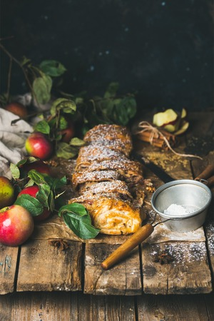sugar powder: Apple strudel cake with cinnamon, sugar powder and fresh apples on rustic wooden table background, selective focus, copy space, vertical composition Stock Photo