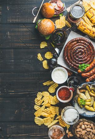 맥주와 스낵 세트. 옥 토 버 페스트 음식 프레임 개념입니다. 다양 한 맥주, 구운 된 소시지, 햄버거, 옥수수, 튀긴 된 감자, 칩, 소금 된 아몬드 및 어두운 나무 배경에 소스. 상위 뷰, 복사본 공간 스톡 콘텐츠 - 64201505