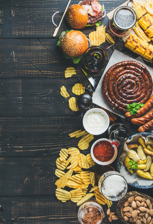 Beer and snack set. Oktoberfest food frame concept. Variety of beers, grilled sausages, burgers, corn, fried potatoes, chips, salted almonds and sauces on dark wooden background. Top view, copy space Фото со стока - 64201505