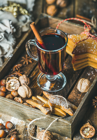 Glass of mulled wine in wooden tray with Christmas decoration toys, gingerbread cookies, nuts, cinnamon, anise and pine cones over rustic wooden background, selective focus, vertical composition