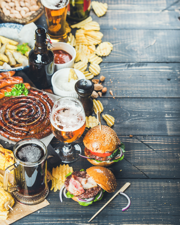 scorched: Beer and snack set. Octoberfest food frame concept. Variety of beers, grilled sausages, burgers, fried potato, corn, chips and sauces on dark wooden scorched background. Selective focus, copy space Stock Photo
