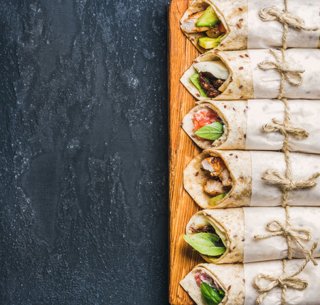 fillings: Tortilla wraps with various fillings on wooden board over dark grey grunge concrete background, top view, copy space. Healthy snack or take-away lunch bites