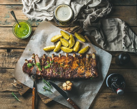 pepperbox: Roasted pork ribs partly cut into pieces with garlic, rosemary, green herb sauce, fried potato and dark beer on rustic wooden background, top view, horizontal composition Stock Photo