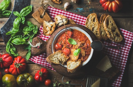 metal grater: Homemade Italian roasted tomato and garlic soup in bowl on round serving board with basil, bread and Parmesan cheese over old rustic wooden background, top view, selective focus, horizontal composition Stock Photo
