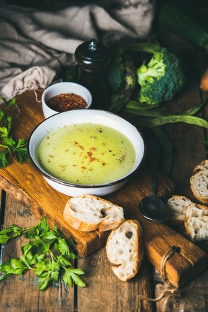 pepperbox: Fresh homemade pea, broccoli, zucchini cream soup in white bowl with fresh baguette slices and parsley on wooden board over rustic background, top view, selective focus, vertical composition Stock Photo