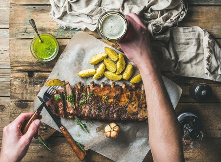 pepperbox: Man eating roasted pork ribs with garlic, rosemary and green herb sauce on rustic wooden table. Man s hands holding fork with fried potato and glass of dark beer, top view
