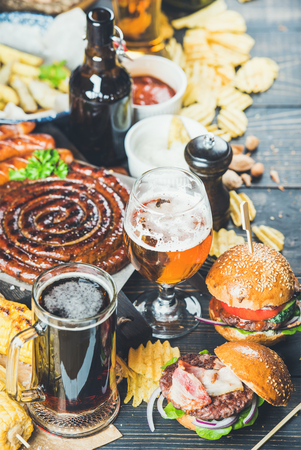 scorched: Beer and snack set. Octoberfest food frame concept. Variety of beers, grilled sausages, burgers, fried potato, corn, chips and sauces on dark wooden scorched background. Selective focus