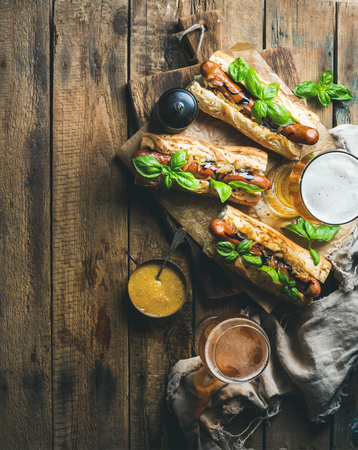 unfiltered: Glasses of wheat unfiltered beer and homemade grilled sausage dogs in baguette with mustard, caramelised onion and herbs on serving board over rustic wooden background, top view, copy space Stock Photo