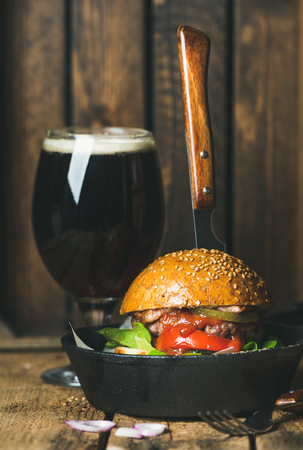 thrust: Homemade beef burger with crispy bacon, fresh vegetables and tomato sauce with knife thrust inside in cast iron pan served with glass of dark beer on rustic wooden background, selective focus