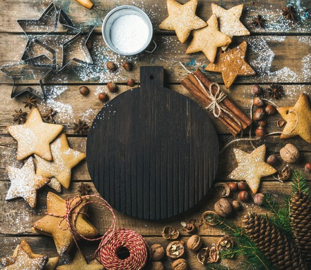 sugar powder: Christmas, New Year background. Gingerbread cookies, sugar powder, nuts, spices, baking molds, fir-tree branch, pine cones on rustic background, dark round wooden board in center, top view, copy space Stock Photo