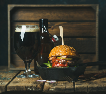 cast iron pan: Homemade beef burger with crispy bacon, fresh vegetables and ketchup in black cast iron pan served with glass of dark beer on rustic wooden background, copy space, horizontal composition