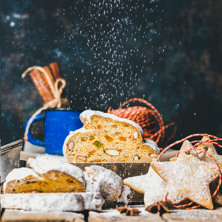 sugar powder: Piece of Traditional German Christmas cake Stollen with festive gingerbread star shaped cookies and falling sugar powder, selective focus, dark blue grunge background, copy space, square crop