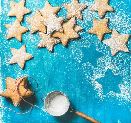 sugar powder: Christmas or New Year holiday food background. Sweet gingerbread cookies in shape of star with sugar powder on bright blue painted plywood background, top view, copy space