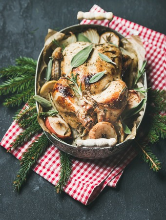 baked meat: Oven roasted whole chicken with onion, apples and sage in serving tray with Christmas table decoration over dark stone background, top view, selective focus. Celebration food concept