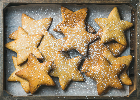 sugar powder: Sweet Christmas holiday gingerbread cookies in shape of stars with sugar powder on baking paper in rustic wooden tray, top view, horizontal composition Stock Photo