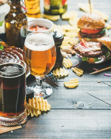 ketchup bottle: Beer and snack set. Octoberfest food frame concept. Beers assortment, grilled sausages, burgers, fried potato, corn, chips and sauces on dark wooden scorched background. Selective focus, copy space