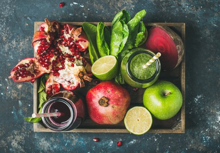 Green and purple fresh juices or smoothies with fruit, greens, vegetables in wooden tray, top view, selective focus. Detox, dieting, clean eating, vegetarian, vegan, fitness, healthy lifestyle concept Stock Photo
