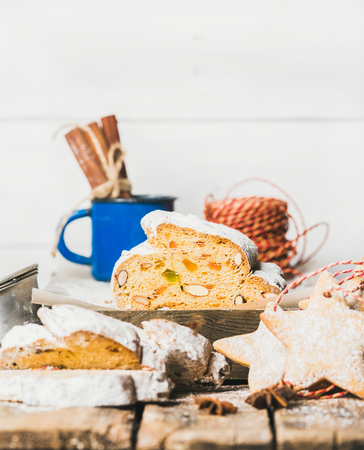 Piece of Traditional German Christmas cake Stollen with festive gingerbread star shaped cookies, selective focus, white background, copy space, vertical composition
