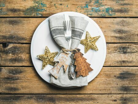 Christmas or New Year holiday rustic table setting. White plate with linen napkin, napkin holders, silverware and golden stars over wooden background. Party or family celebration concept