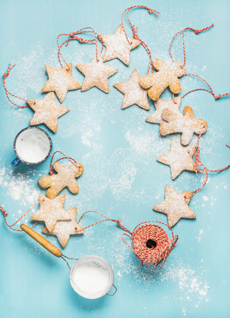 sugar powder: Christmas homemade gingerbread star shaped cookies with sugar powder, milk and red decoration rope over blue background, top view, copy space, vertical composition