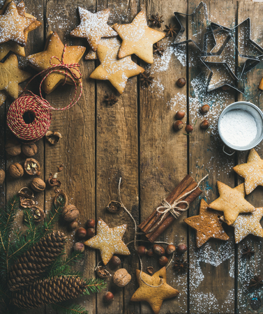 sugar powder: Christmas or new year background. Star shaped gingerbread cookies with sugar powder, nuts, cinnamon, anise, decorative rope, fir tree branch, pine cones on wooden background, top view, copy space Stock Photo