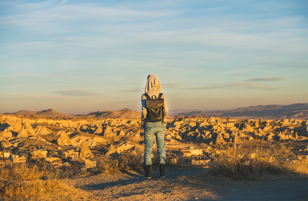 Young woman traveller wearing hoodie, backpack and jeans standing and watching sunrise in mountains over Goreme, Cappadocia, Central Turkey Stock Photo