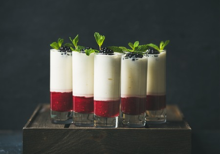 christmas catering: Catering, banquet or party food concept. Dessert in glass with blackberries and mint leaves over dark background on corporate event, christmas, birthday, wedding celebration, selective focus
