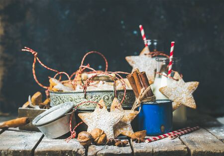 sugar powder: Christmas festive star shaped gingerbread cookies or biscuits in vintage tray, decoration rope, nuts, spices, milk for Santa in bottles with straws, sugar powder. Selective focus, copy space