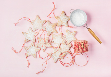 sugar powder: Christmas homemade gingerbread star shaped cookies with sugar powder in sieve and red decoration rope over light pink background, top view, horizontal composition