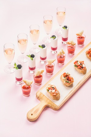 christmas catering: Catering, banquet, party food concept. Various snacks, brushetta sandwiches, gazpacho shots, desserts on corporate event, christmas, birthday, wedding celebration over pink background, selective focus Stock Photo
