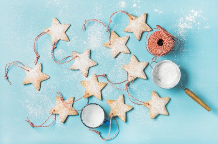 sugar powder: Christmas homemade gingerbread star shaped cookies with sugar powder and red decoration rope over blue background, top view, horizontal composition Stock Photo