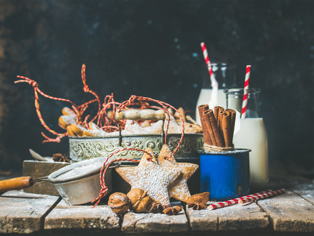 sugar powder: Christmas festive star shaped gingerbread cookies or biscuits in vintage tray, decoration rope, nuts, spices, milk for Santa in bottles, sugar powder. Selective focus, copy space