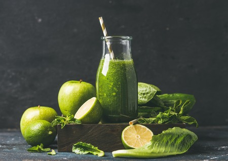 romaine lettuce: Green smoothie in glass bottle with apple, romaine lettuce, lime and mint, dark background, selective focus. Detox, dieting, clean eating, vegetarian, vegan, fitness or healthy lifestyle concept Stock Photo