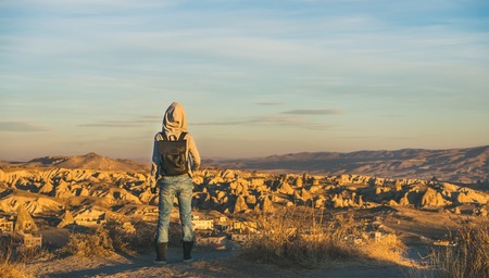 Young woman traveller wearing hoodie, backpack and jeans watching sunrise in the mountains over Goreme, Cappadocia, Central Turkey