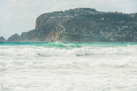 Stormy Mediterranean sea in winter in Alanya, Turlkey. View over Alanya castle hill and waves on clear day