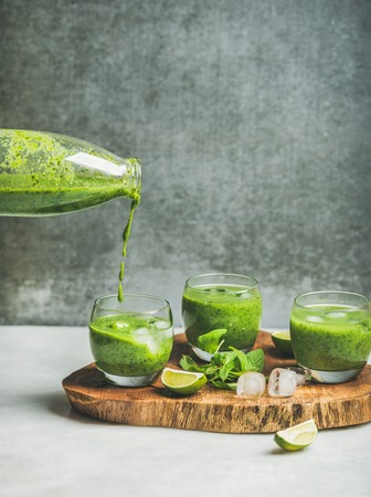 Fresh green smoothie in glasses and pouring from bottle with ice cubes, mint, lime on wooden board, grey concrete wall at background, selective focus, copy space. Clean eating, healthy food concept