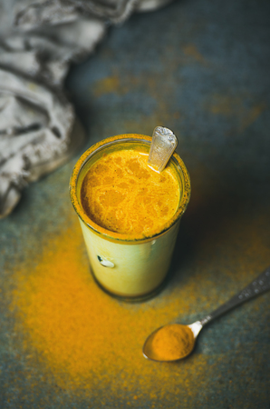 Golden milk with turmeric powder in glass over dark background, copy space. Health and energy boosting, flu remedy, natural cold fighting drink. Clean eating, detox, weight loss concept